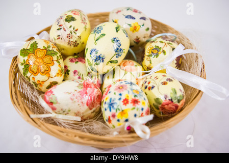 Group of colorful easter eggs decorated with flowers made by decoupage technique, in a basket on light background - Stock Photo