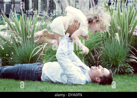 Father lying on grass, playfully lifting young daughter in air - Stock Photo