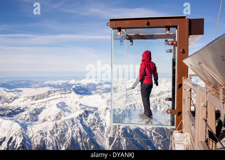 A tourist stands in the 'Step into the Void' glass box on the Aiguille Du Midi (3842m) mountain top above Chamonix - Stock Photo