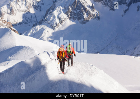 Mountaineers descend from a lookout point on the Aiguille Du Midi (3842m) mountain top above Chamonix Mont-Blanc. - Stock Photo