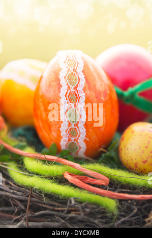 orange decorative egg with ribbons and lace trimmings in bird nest for easter - Stock Photo