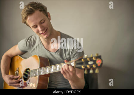 A beautiful young man playing acoustic guitar. - Stock Photo