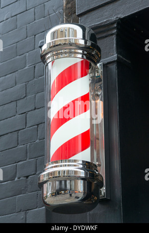 A red and white barber shop pole on a wall outside a shop in the UK - Stock Photo
