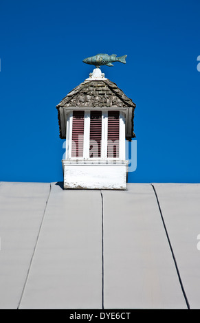 Vintage rooftop cupola with an unusual fish wind vane and blue sky on a barn in Vermont, USA, New England, American - Stock Photo