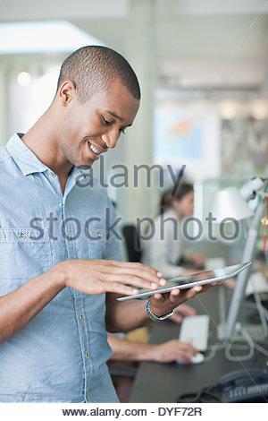 Man using digital tablet in office - Stock Photo