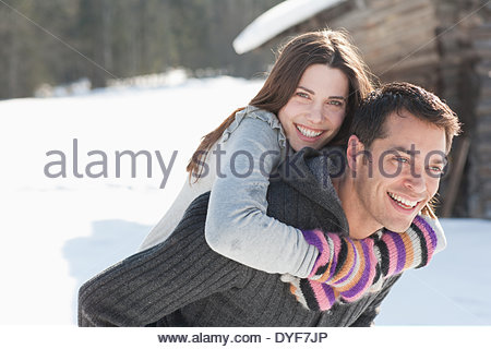 Man giving girlfriend piggyback ride - Stock Photo