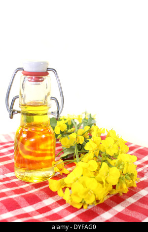 a bottle of rapeseed oil and rapeseed flowers against white background - Stock Photo