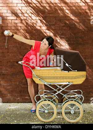 A woman taking a photograph with her baby in a pram. - Stock Photo