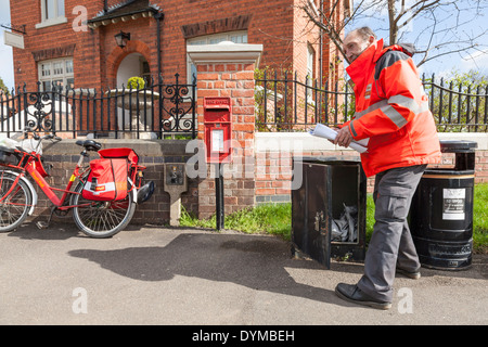 Royal Mail postman collecting post from a box prior to delivering. Nottinghamshire, England, UK - Stock Photo