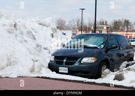 Car blocked by high plowed snow - USA - Stock Photo
