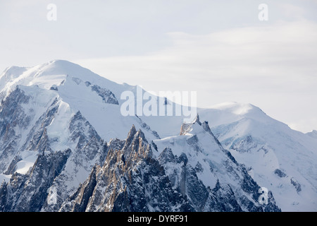 The Aiguille Du Midi gondola station (R), with Mont Blanc mountain in the background (C), seen from the top of Grand - Stock Photo