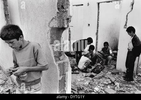Children play in the ruins in Kosovo - Stock Photo