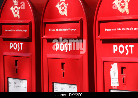 3 red post boxes and and white wall in denmark - Stock Photo