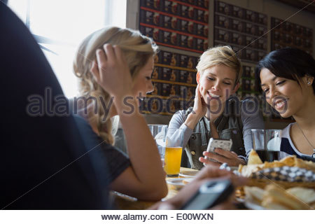 Friends text messaging with cell phones at brewery - Stock Photo