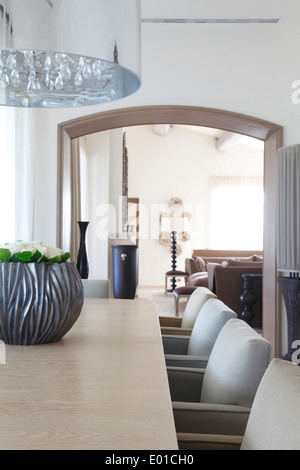 Detail of modern chandelier over dining table and dining chairs in subtly differing pale shades sitting room lies - Stock Photo