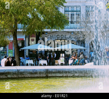 Art Deco style Nicola cafe terrace seen from fountain in Rossio Square (Praca Dom Pedro 1V) Lisbon Portugal western - Stock Photo
