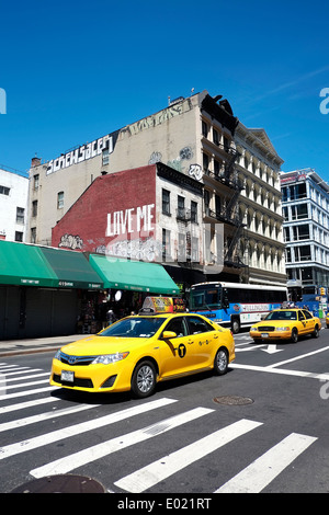 Iconic New York City taxi cabs wait at an intersection in Manhattan. - Stock Photo