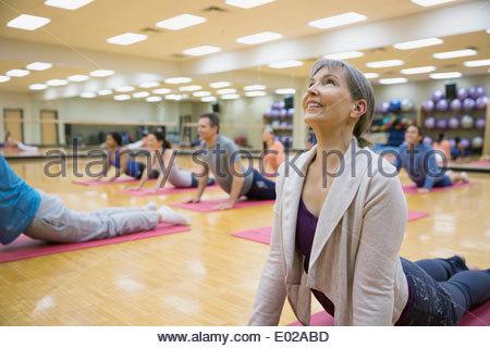 Group practicing upward facing dog in yoga class - Stock Photo