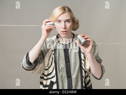 Blonde woman using tin can phone. Conceptual image of connection and communication. - Stock Photo