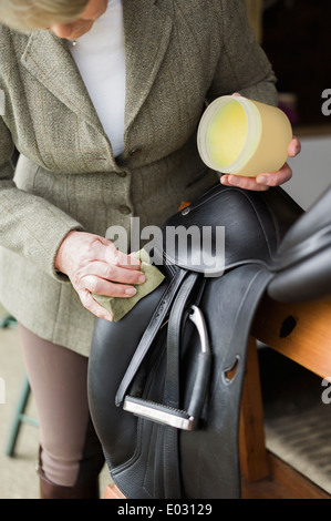 A woman cleaning and preparing tack and saddle in the courtyard of a riding stable. - Stock Photo