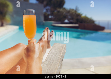 Young woman holding fruit juice while sitting on a deck chair. Female model sunbathing near swimming pool with a - Stock Photo