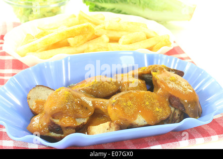 Currywurst with french fries on a checkered napkin before light background - Stock Photo