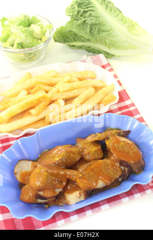 Currywurst with french fries with salad on a light background - Stock Photo
