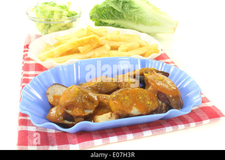 Currywurst with french fries on a napkin before light background - Stock Photo
