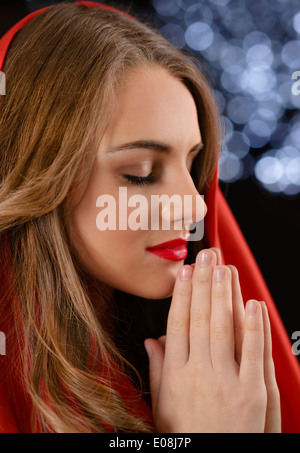 Beautiful woman praying with blurred lights in background - Stock Photo