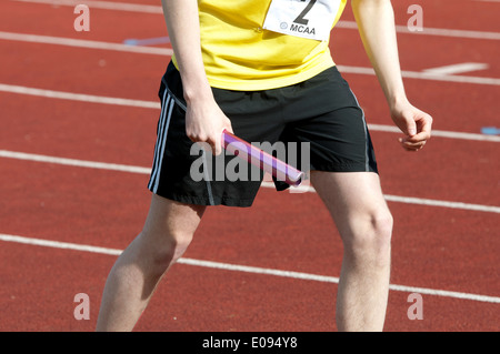 Athletics, runner with baton at start of men`s 4X400m relay race at club level, UK - Stock Photo