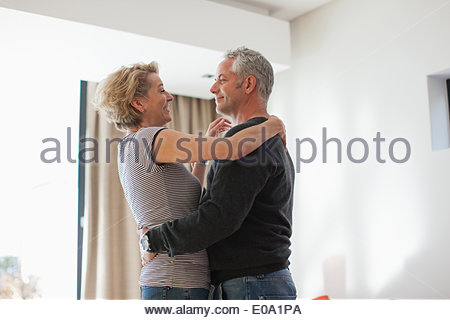 Mature couple dancing in living room - Stock Photo