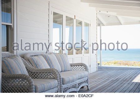 Deck chairs on porch of beach house - Stock Photo