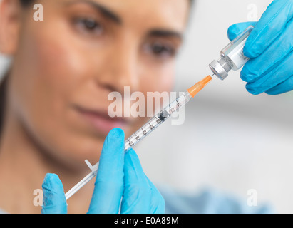 Close up of nurse preparing a syringe for an injection - Stock Photo