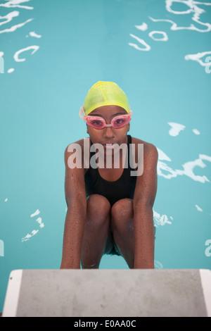Portrait of confident schoolgirl swimmer poolside - Stock Photo