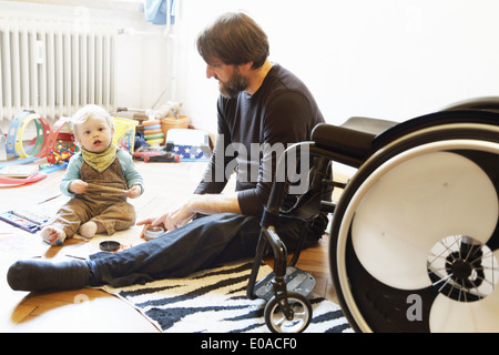 Disabled father with son playing on floor - Stock Photo