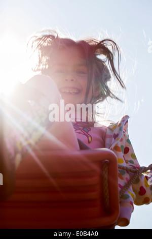Portrait of smiling little girl on swing - Stock Photo