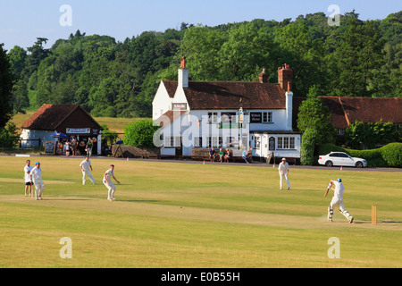 Local teams playing a cricket match on a village green in front of Barley Mow pub on a summer's evening. Tilford - Stock Photo