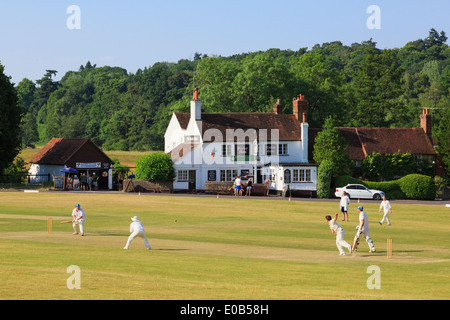 Local teams playing a cricket match on village green in front of Barley Mow pub on a summer's evening. Tilford Surrey - Stock Photo