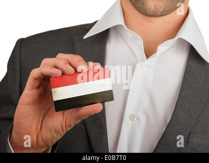 Businessman is holding a business card  flag of Yemen - Stock Photo