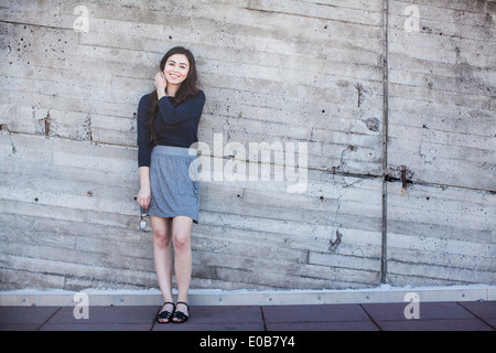 Young woman standing, leaning against wall - Stock Photo