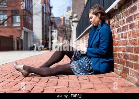 Young woman sitting against a brick wall using smartphone - Stock Photo