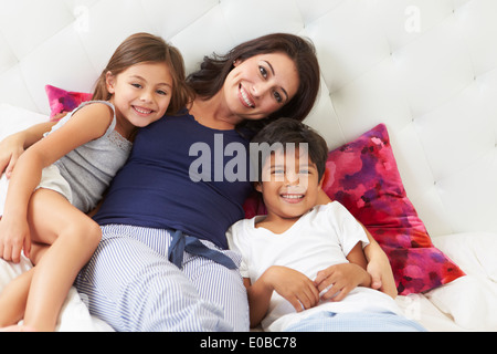 Mother And Children Relaxing In Bed Wearing Pajamas - Stock Photo
