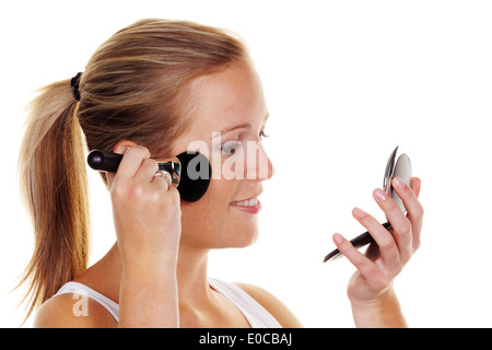 A young woman with paintbrush and pocket mirror with the greasepaint, Eine junge Frau mit Pinsel und Taschenspiegel - Stock Photo