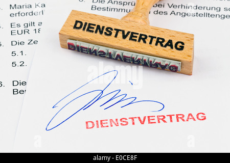 A stamp of wood lies on a document. Label Contract of employment, Ein Stempel aus Holz liegt auf einem Dokument. - Stock Photo