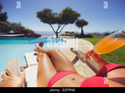 Female model in red bikini lying on a deck chair drinking a juice on a sunny day by swimming pool. Young woman sunbathing. - Stock Photo