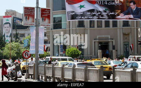 Damascus, Syria. 12th May, 2014. Syrians walk past election posters in Damascus, Syria, May 12, 2014. A day earlier, - Stock Photo