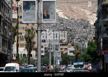 Damascus, Syria. 12th May, 2014. Cars run past election posters in Damascus, Syria, May 12, 2014. A day earlier, - Stock Photo
