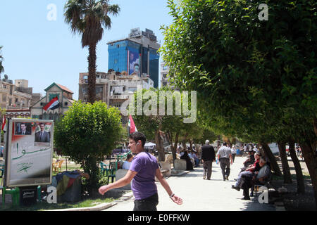 Damascus, Syria. 12th May, 2014. A man walks past a election poster in Damascus, Syria, May 12, 2014. A day earlier, - Stock Photo