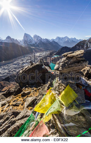 Prayer Flags And Rock Cairn Above Glacier And Valley In Himalayas With Sun, Gokyo Ri, Nepal, Asia - Stock Photo