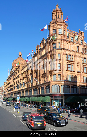 Brompton Road and Harrods luxury department store listed building in Knightsbridge on a blue sky day in West London - Stock Photo